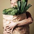 Man holding bag full of green vegetables — Stock Photo #25981143
