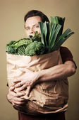 Adam holding torbalı yeşil sebze dolu — Stok fotoğraf