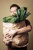 Man innehav väska full med gröna grönsaker — Stockfoto