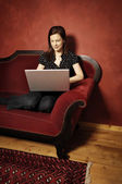 Woman on red sofa serie — Stock Photo