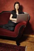женщина на красном диване серия — Стоковое фото