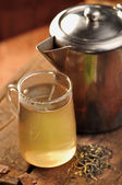 Glass mug with green tea and teapot — Stock Photo