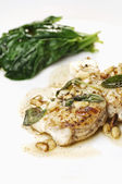 Fried monkfish with butter and sage and pine nuts, fried garlic and some green spinach in the background — Stock Photo