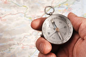 Hand holding compass, map out of focus in the background — Foto Stock