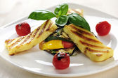Grilled Halloumi cheese on grilled vegetables with basil — Stock Photo