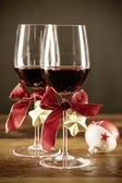Two glasses of red wine with christmas ornaments — Stock Photo