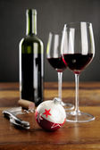 Two glasses of red wine and christmas baubel — Stock Photo
