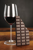 Glass of red wine and chocolate bar — ストック写真