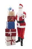 Santa claus met gestapelde kerst presenteert — Stockfoto