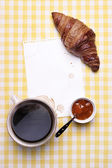 Breakfast scene with Coffee, Croissant, Jam and Blank Paper — Stock Photo