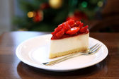Cheesecake with strawberries on a festive New Year's table on the background of trees — Stock Photo