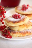 Delicious homemade cheese pancakes with berries and redcurrant. Sprinkled with powdered sugar — Stock Photo