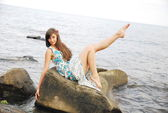 Young girl with long dark hair posing on the huge rocks by the sea — Stock Photo