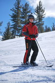 Athlete skier posing on mountain resort of Bansko in Bulgaria on a sunny winter day. — Stock Photo