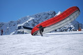Paraglider dispersed on top of the mountain Todorka Bansko ski resort in Bulgaria on a sunny winter day. — Stock Photo
