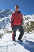 Young man on a mountain top Todorka on Bansko ski resort in Bulgaria sunny winter day — Stock Photo