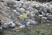 Young man on the rocky shore of a mountain stream near the ski resort of Bansko in Bulgaria — Stock Photo