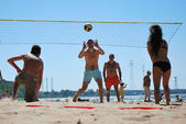 Young people playing beach volleyball on the sand near the water dam — Stock Photo