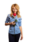 Attractive blonde woman holding a flower — Stock Photo