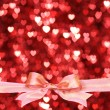 Glossy pink bow with a lot of hearts background. — Stock Photo