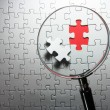 Search for missing puzzle pieces with a magnifying glass. — Stock Photo