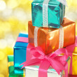 Pile of small gifts on gold blurry lights background.(vertical) — Stock Photo #19067973