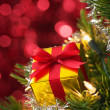 Small gift on Christmas tree.(vertical) — Stock Photo
