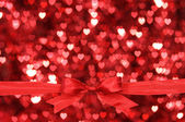 Red bow with a lot of hearts background. — Stock Photo