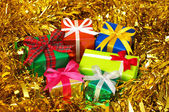 Five colorful gifts on gold tinsel.(horizontal) — Stockfoto