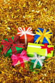 Five colorful gifts on gold tinsel.(vertical) — Stok fotoğraf