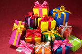 Pile of small gifts on red background. — Stock Photo