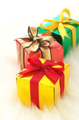 Three gifts on white fake fur background. (vertical) — Foto de Stock