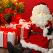 Stuffed toy Santa Claus and many Christmas presents. — Stock Photo