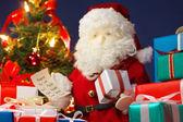 Santa Claus preparing Christmas presents. (horizontal) — Stock Photo