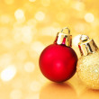 Christmas balls on gold sparkle background. — Stock Photo