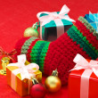 Christmas stocking and colorful christmas presents on red fabric — Stock Photo