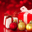 Stock Photo: Small presents on red sparkle background.