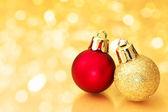 Christmas balls on gold sparkle background. — Stock Photo