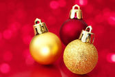 Close up of Christmas balls on red sparkle background. — Stock Photo