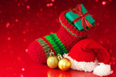 Small Christmas stocking and Santa hat on red sparkle background — Stock Photo