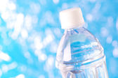 Bottle of water on defocused sparkle background. — Stock Photo