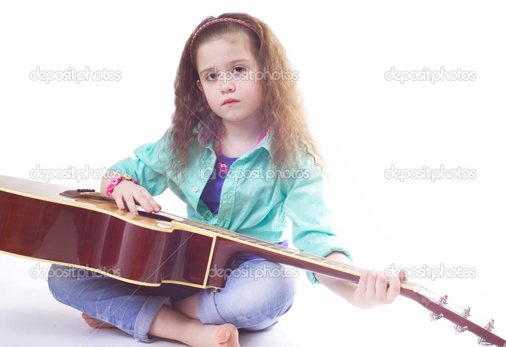 膝盖上抱着吉他的可爱小女孩