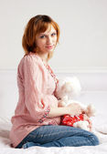 The smiling beautiful pregnant woman with a plush toy — Stock Photo