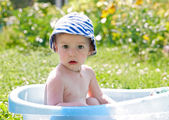 Little baby (1 year) sitting in the bath in nature — Stock Photo