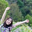 Asian woman relaxing in the flowers garden — Stock Photo