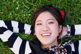 Asian woman lying on the grass — Stock Photo