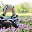 Stock Photo: Asiwomreading booklet on grass