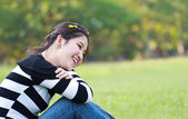Asian woman relaxing on the grass — Stock Photo