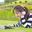 Young woman using tablet on grass — Stock Photo