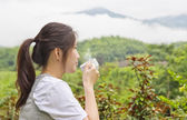 Young woman drinking coffee at mountain view — Stock Photo